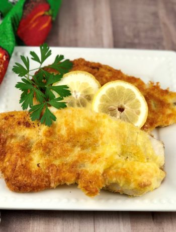 """FODMAP foods - Gluten Free """"fried"""" fish with lemon and parsley on a white plate"""