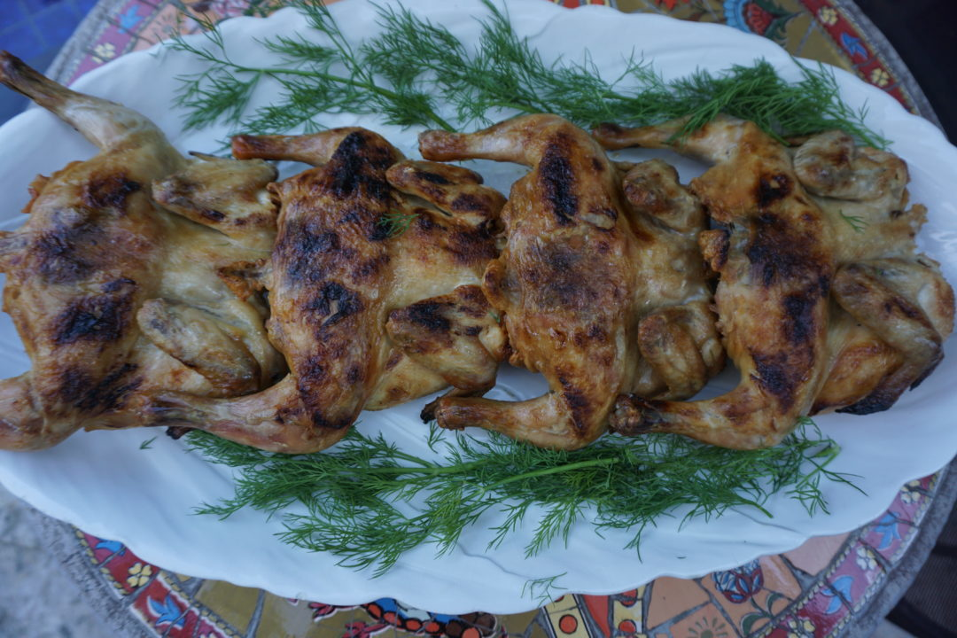 Cooked Cornish Hens on a white platter with dill