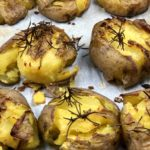Smashed Potatoes topped with salt, rosemary and olive oil on a parchment lined baking sheet. - FODMAP smashed dish