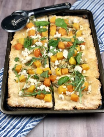 Butternut squash, arugula, ricotta & pumpkin seed topped gluten free pizza on a rectangular baking sheet.