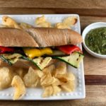 FODMAP safe grilled vegetable sandwich with chips and a side of pesto on a white plate.